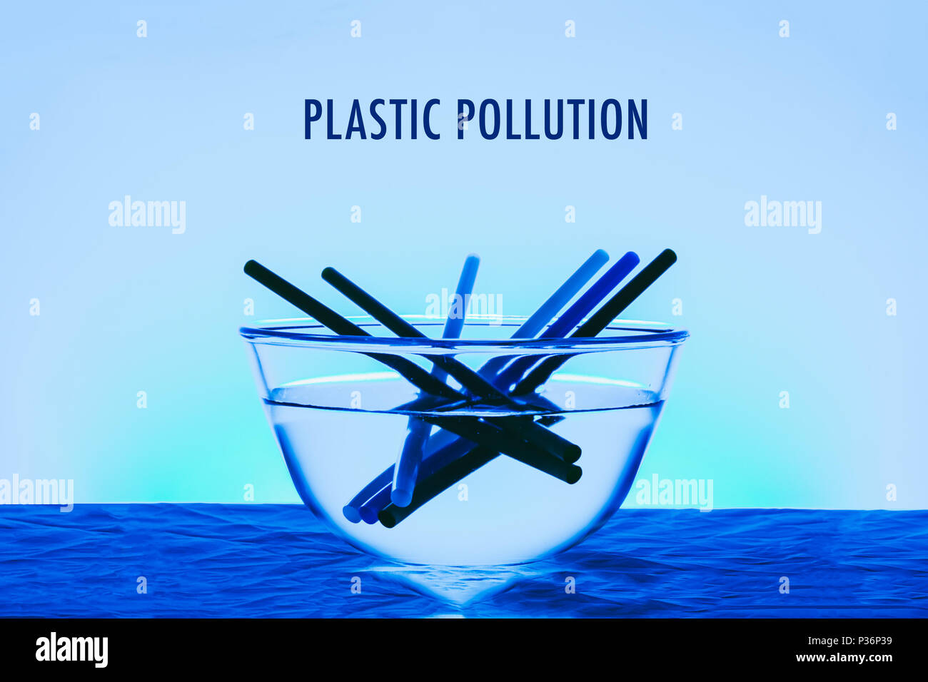 Plastic pollution title in the ocean concept photo with glass of bowl and plastic straw blue color effect - Stock Image