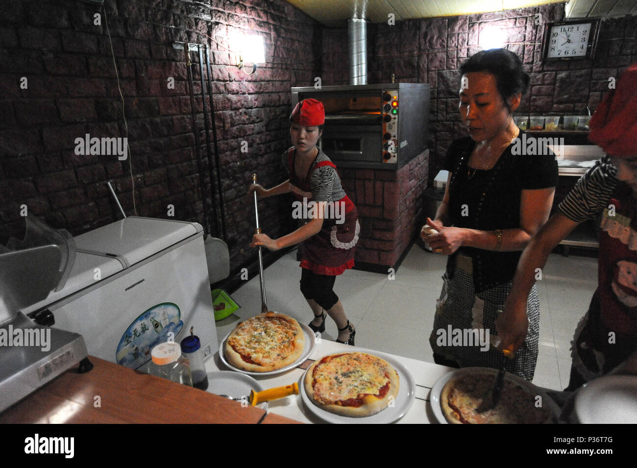 Pjoengjang, North Korea, co-workers in the kitchen of a pizzeria - Stock Image