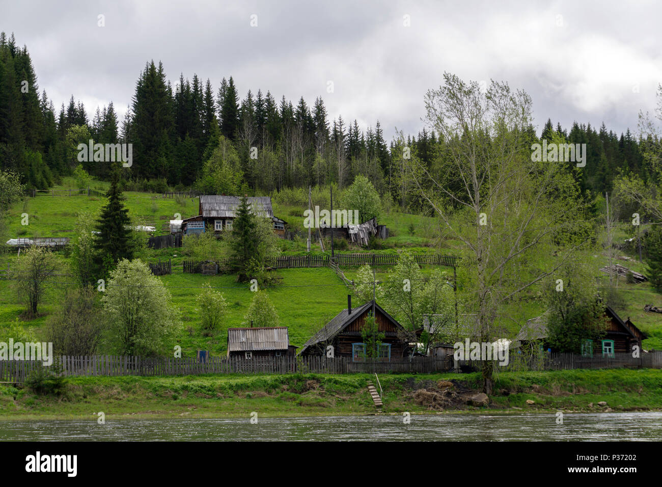 landscape of a small Ural village with wooden huts on the river bank in the forest on a cloudy day - Stock Image