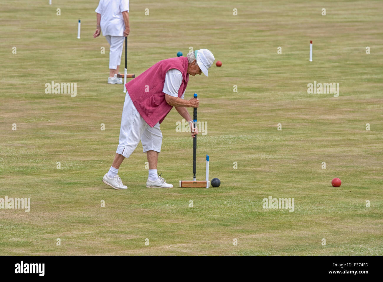 Older woman playing croquet - Stock Image