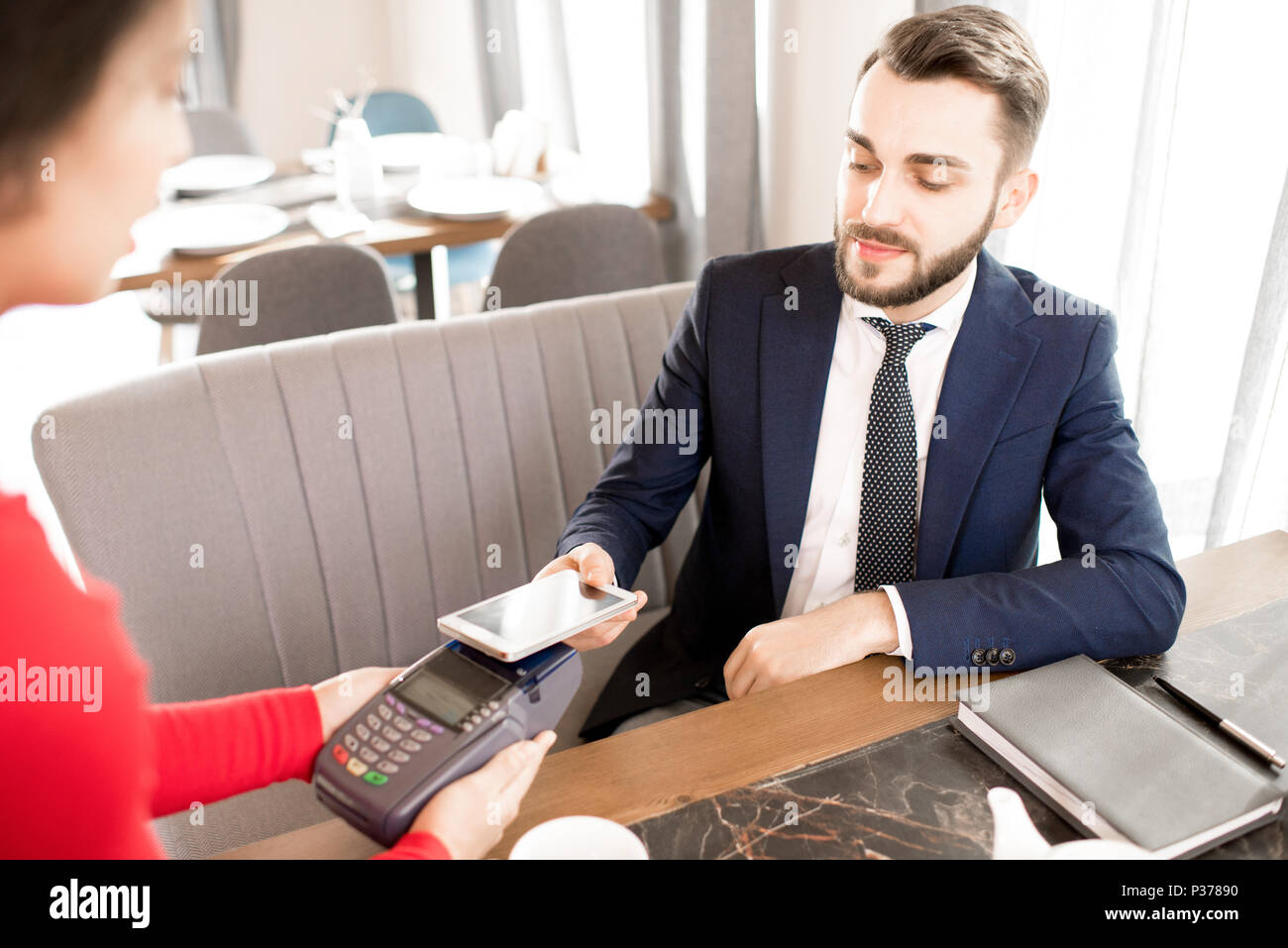 Businessman paying for lunch with smartphone - Stock Image