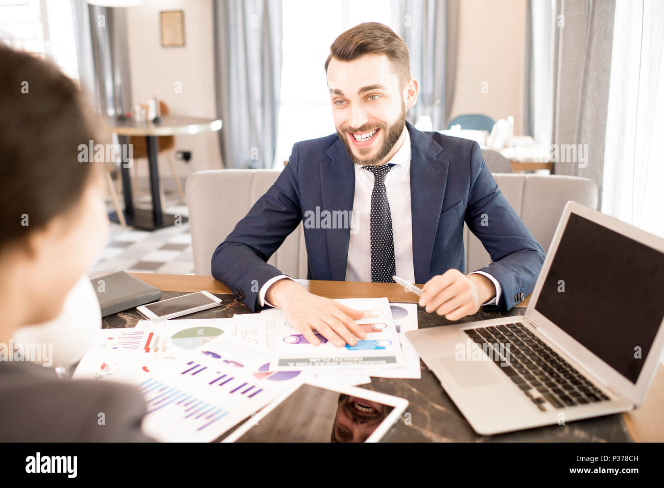 Excited business analyst working with colleague in cafe - Stock Image