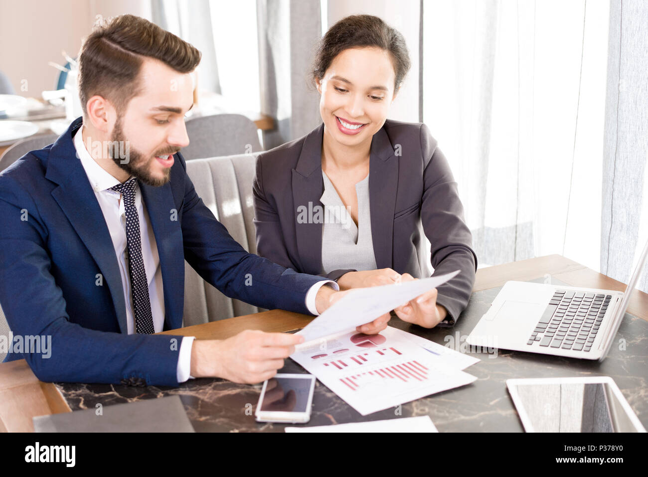 Optimistic forecasting managers discussing papers - Stock Image