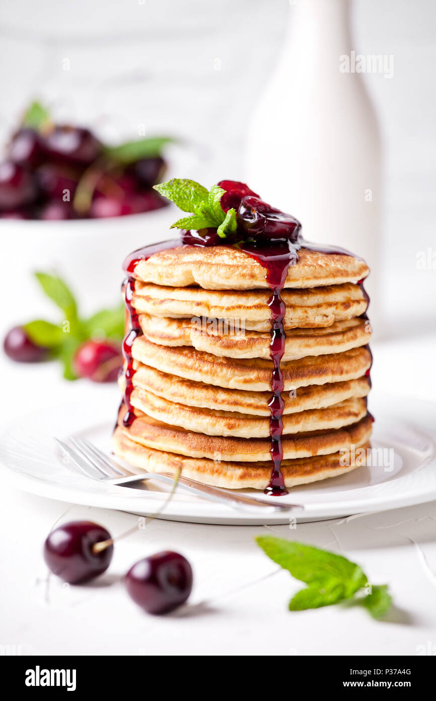 Bunch of homemade pancakes with cherry topping - Stock Image