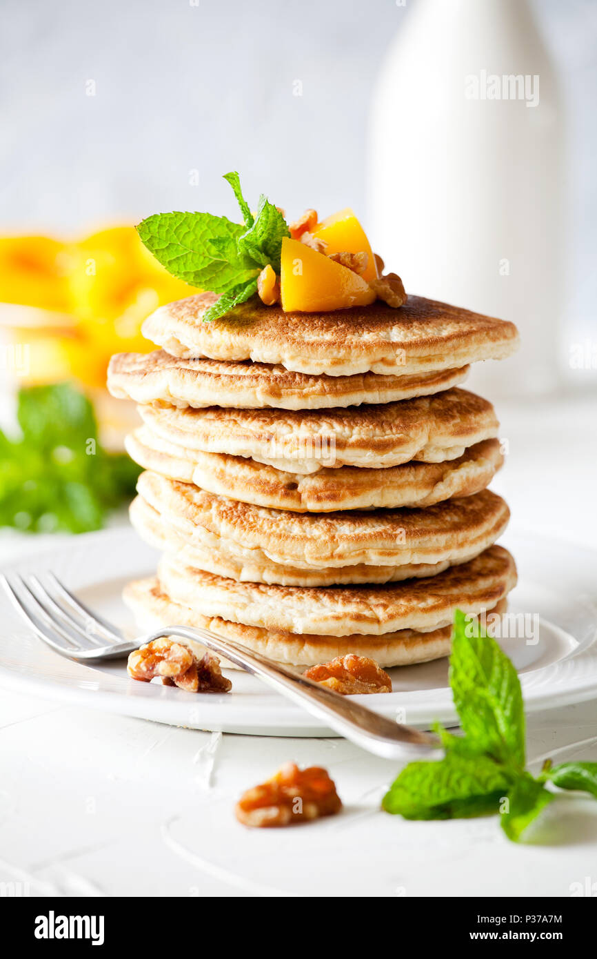 Bunch of pancakes with poached peaches and nuts - Stock Image