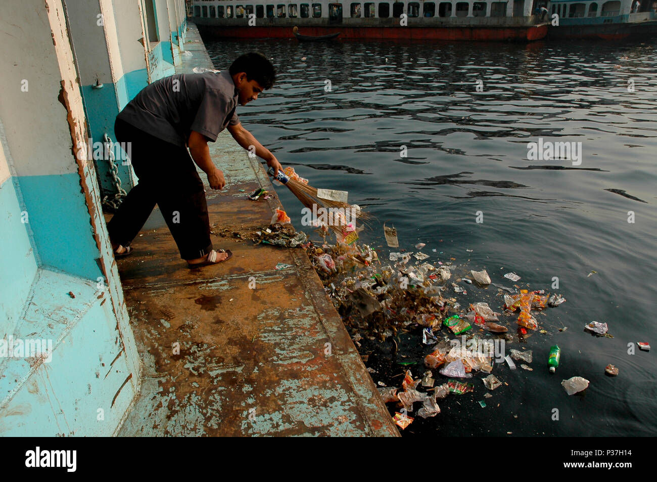 A man sweeps floor of the launch and puts rubbish on the Buriganga River. Dhaka, Bangladesh. - Stock Image