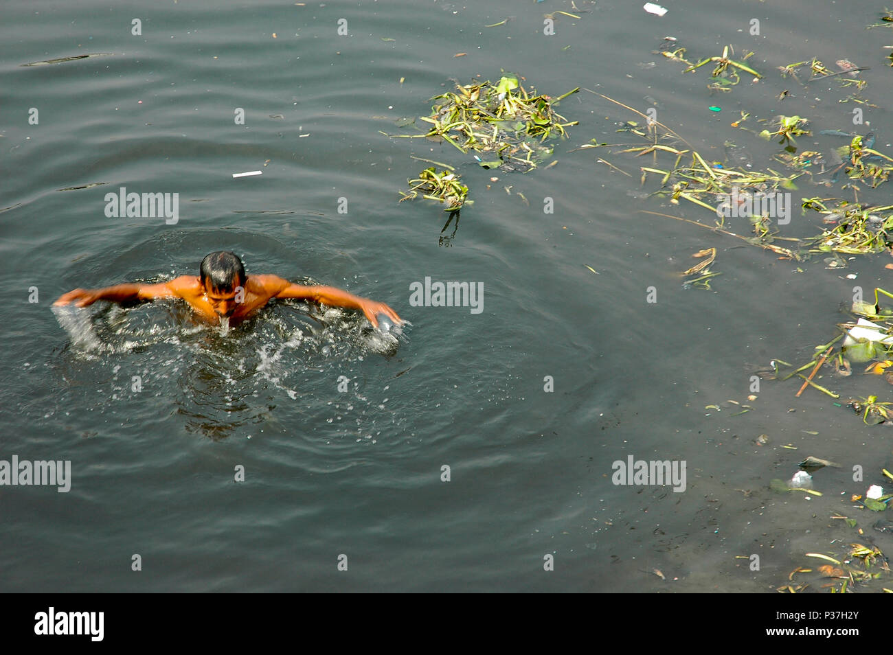 A man taking bath in the poisonous and dirty water of the