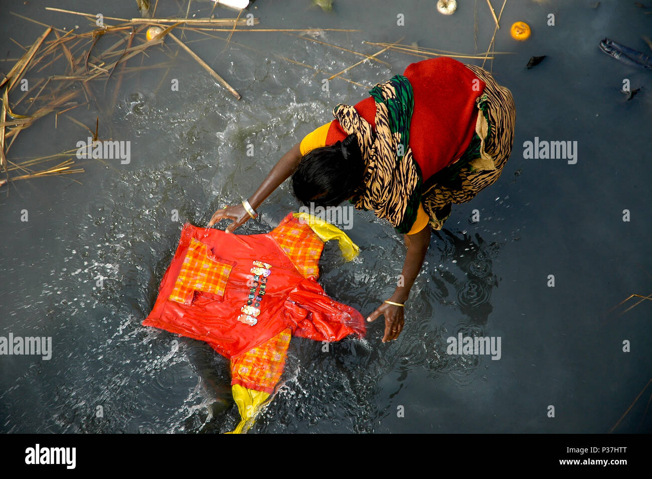 A woman washes cloth in the poisonous and dirty water of Buriganga River. Dhaka, Bangladesh - Stock Image