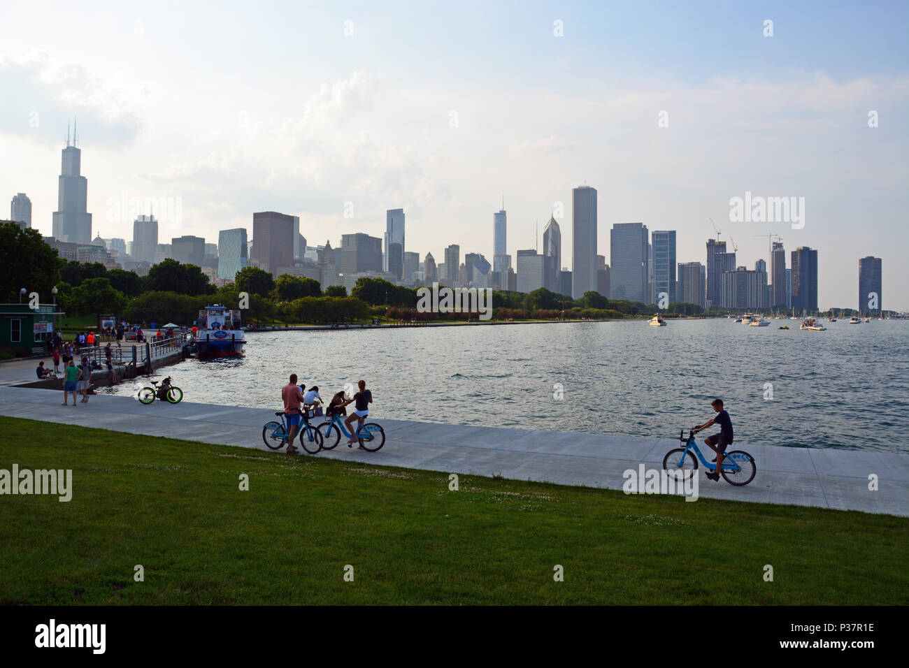 Visitors to Chicago ride Divvy bikes along the lakefront on the Museum Campus with the city skyline in the background. - Stock Image