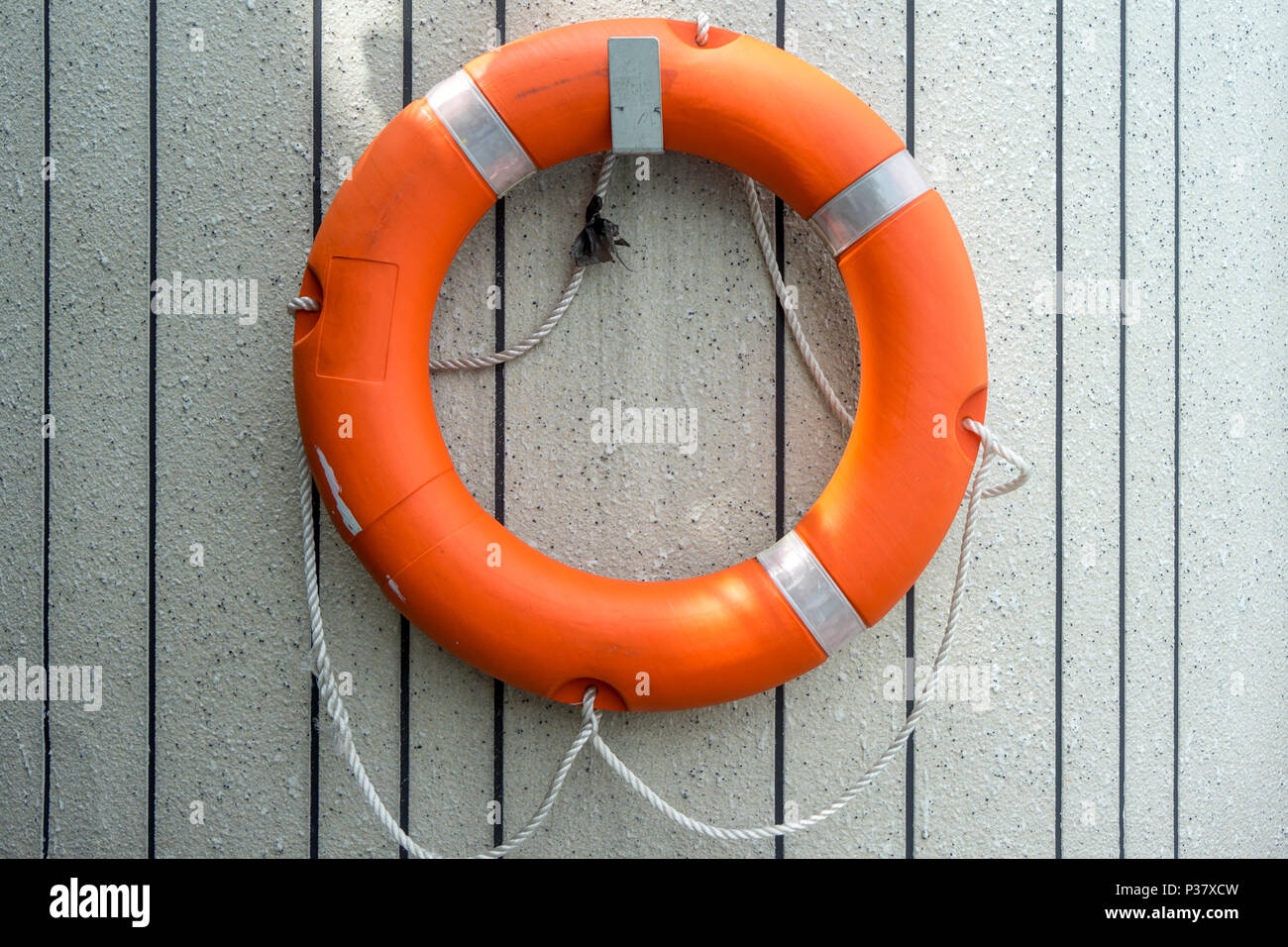 Orange Lifebuoy Hanging On Stone Cement Wall Water Rescue Emergency
