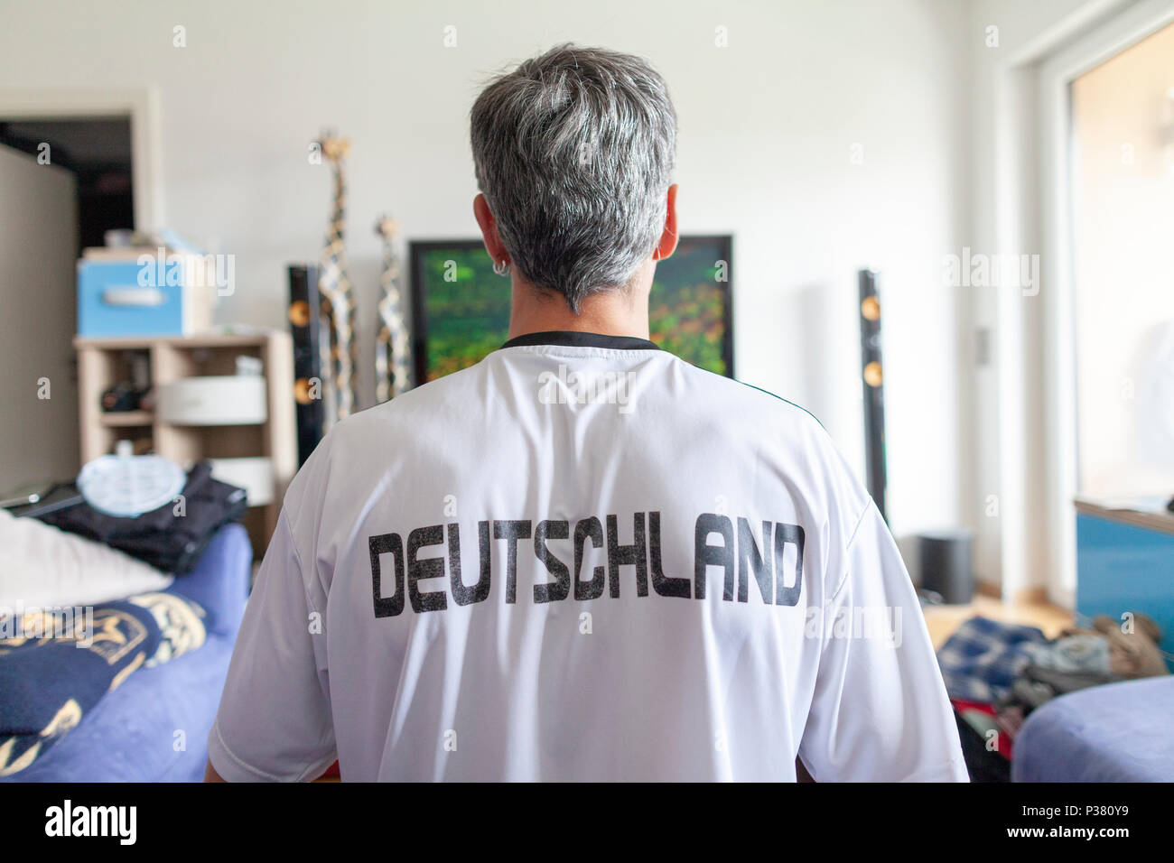 German fan sits in a Deutschland ( Germany ) jersey in front of a television - Stock Image