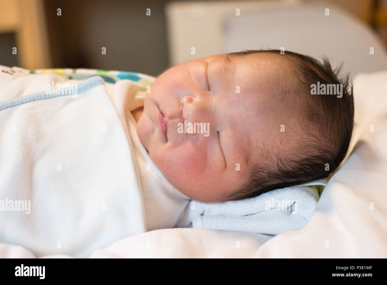 An Asian new born baby falling into a deep sleep - Stock Image