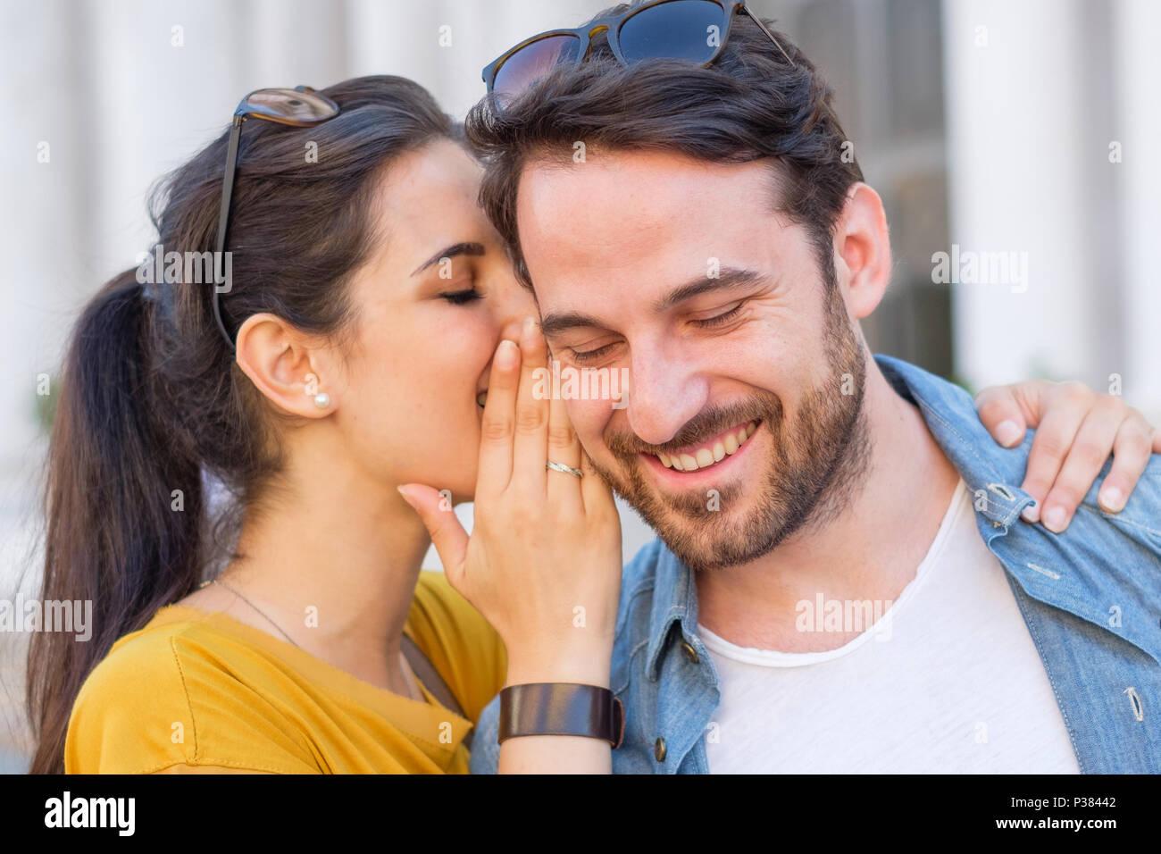 Woman is whispering a secret into his boyfriends ear - Stock Image