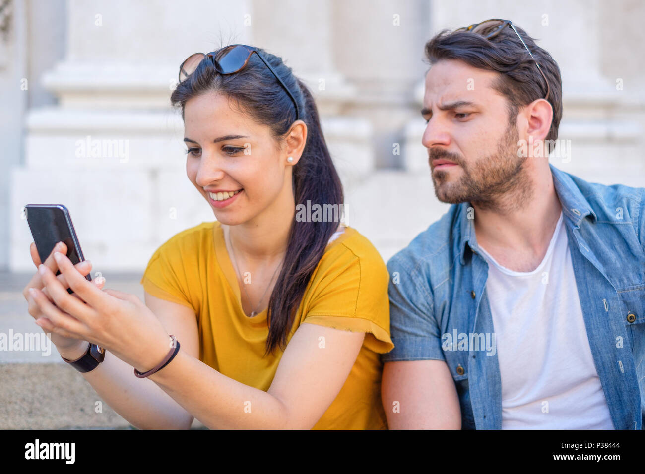 Suspicious boyfriend spying his girlfriend texting on mobile phone - Stock Image
