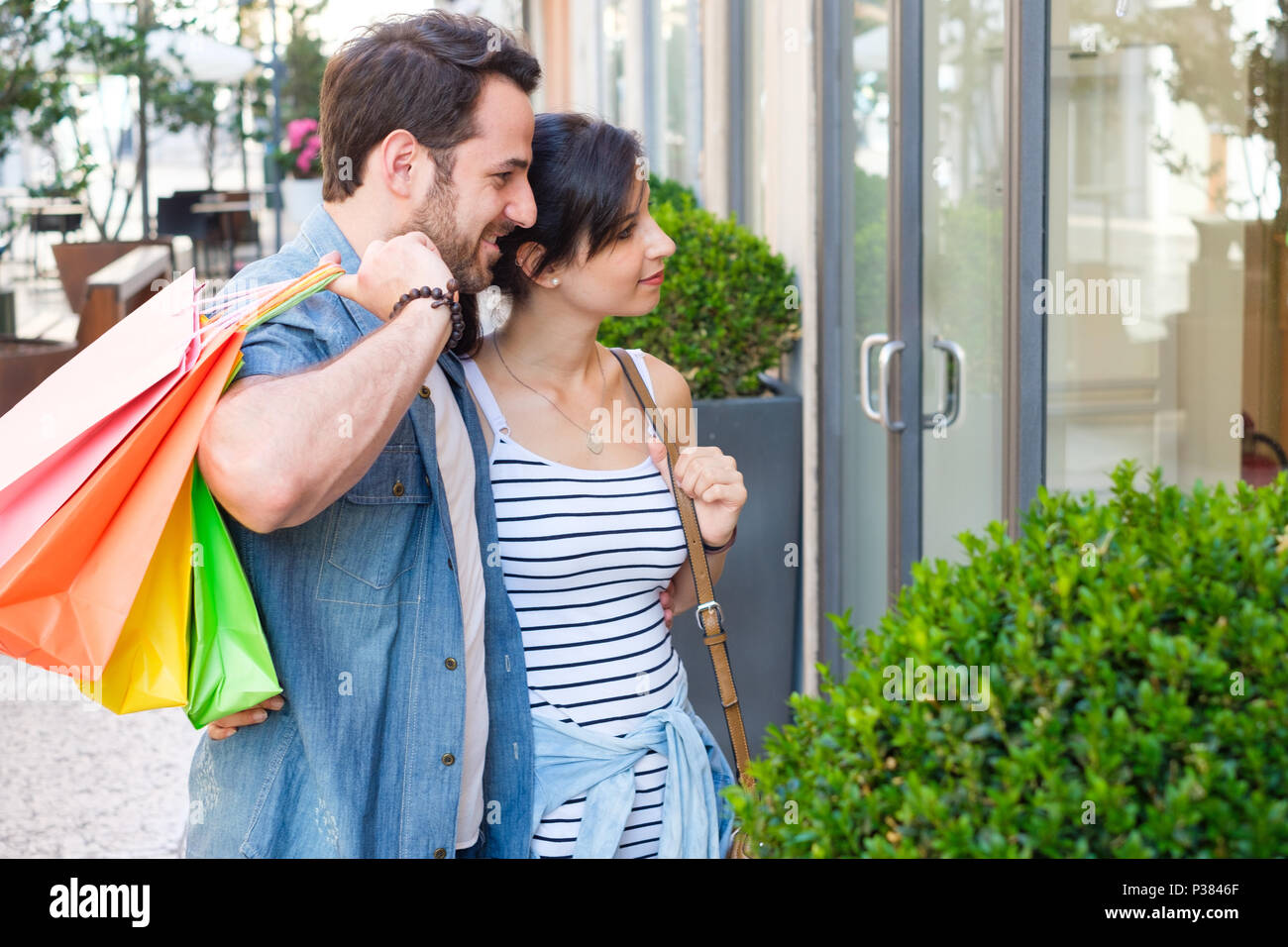 Young happy couple with shopping bags in the city during seasonal sales - Stock Image
