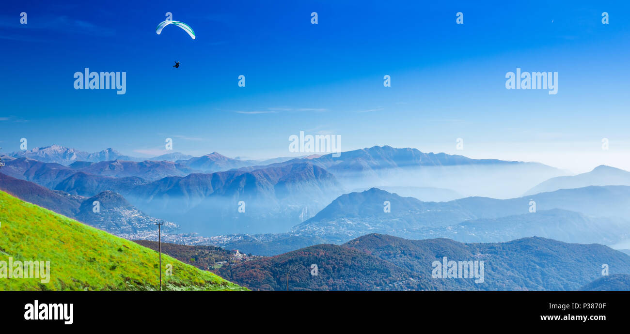 Paraglider over the Lugano city, San Salvatore mountain and Lugano lake seen from Monte Lema, Canton Ticino, Switzerland Stock Photo