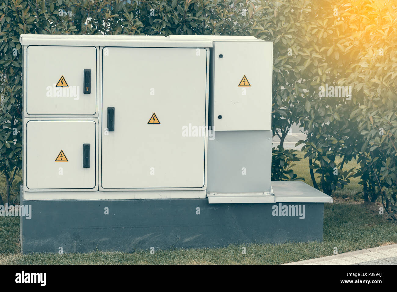 Outdoor plastic electrical cabinet with warning signs. An electrical enclosure is a cabinet for electrical or electronic equipment to mount switches,  Stock Photo