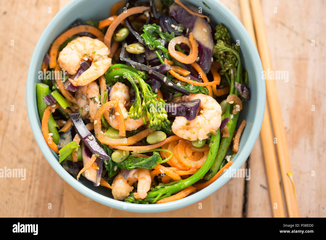 Stir fry with carrots, red cabbage, broccoli, kale, edamame, spring onions, seeds & prawns - Stock Image