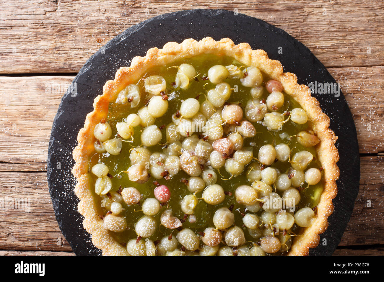 Homemade pie with summer gooseberries and  jam closeup in a board. horizontal top view from above Stock Photo