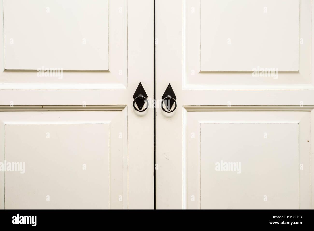 Vintage white wooden cupboard doors with metal handles - Stock Image
