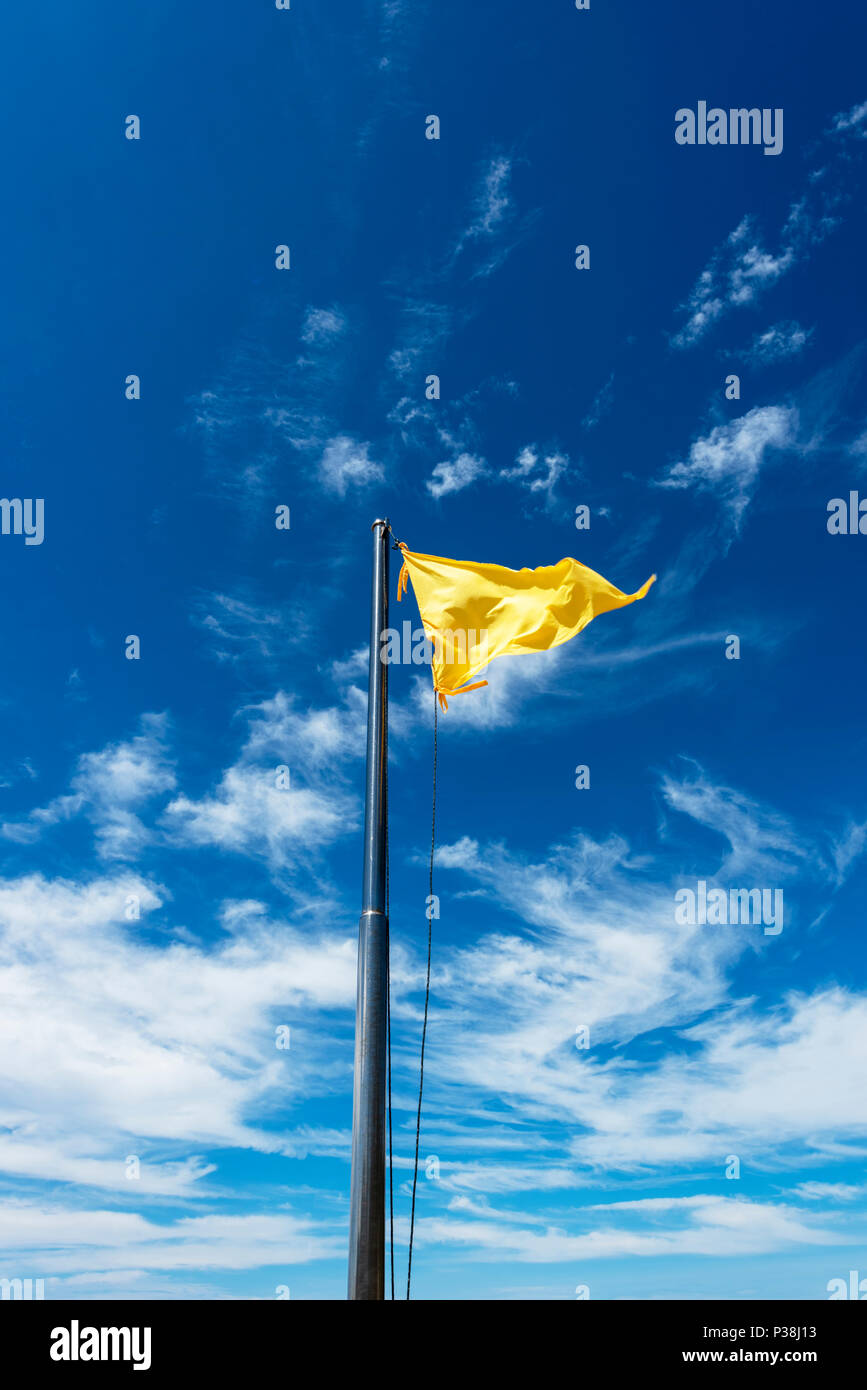 Yellow flag on a pole fluttering in the breeze against a bright blue sky in Kota Kinabalu, Borneo - Stock Image