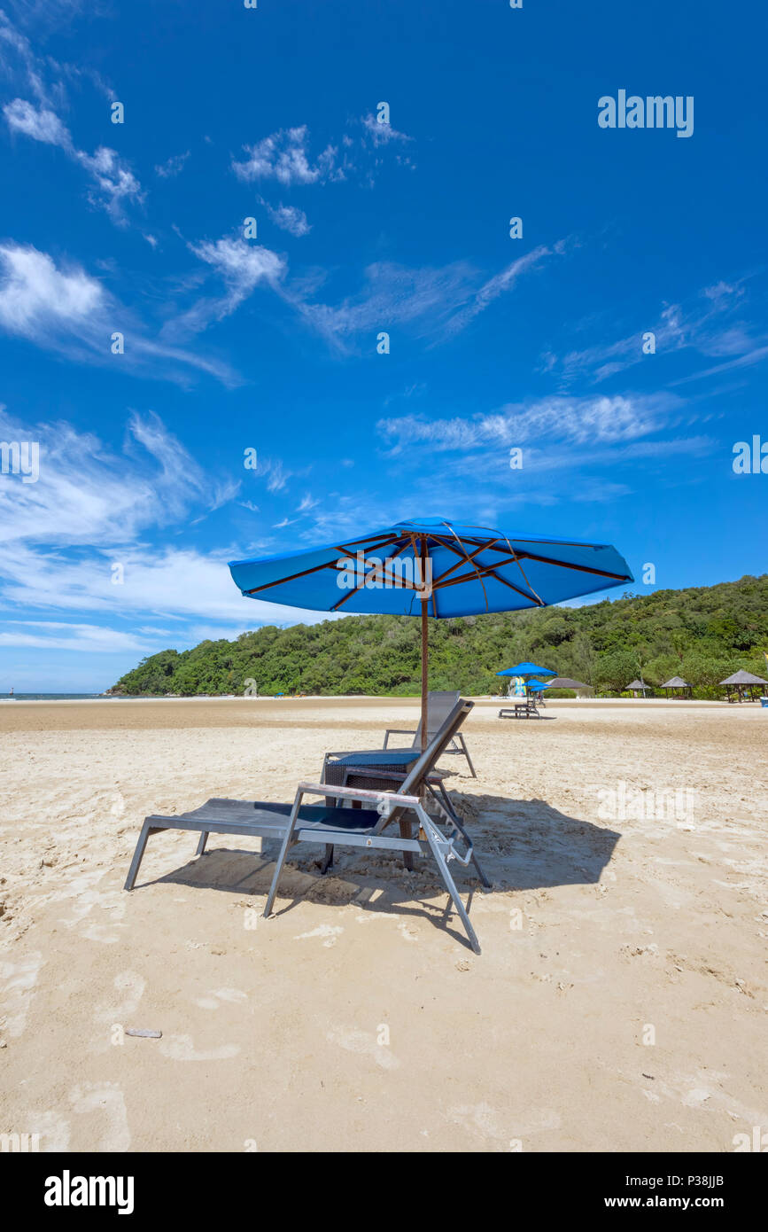 Sunbeds and Parasol on a white sand beach at the Shangri La Rasa Ria Hotel and Resort in Kota Kinabalu, Borneo on the edge of the South China Sea - Stock Image