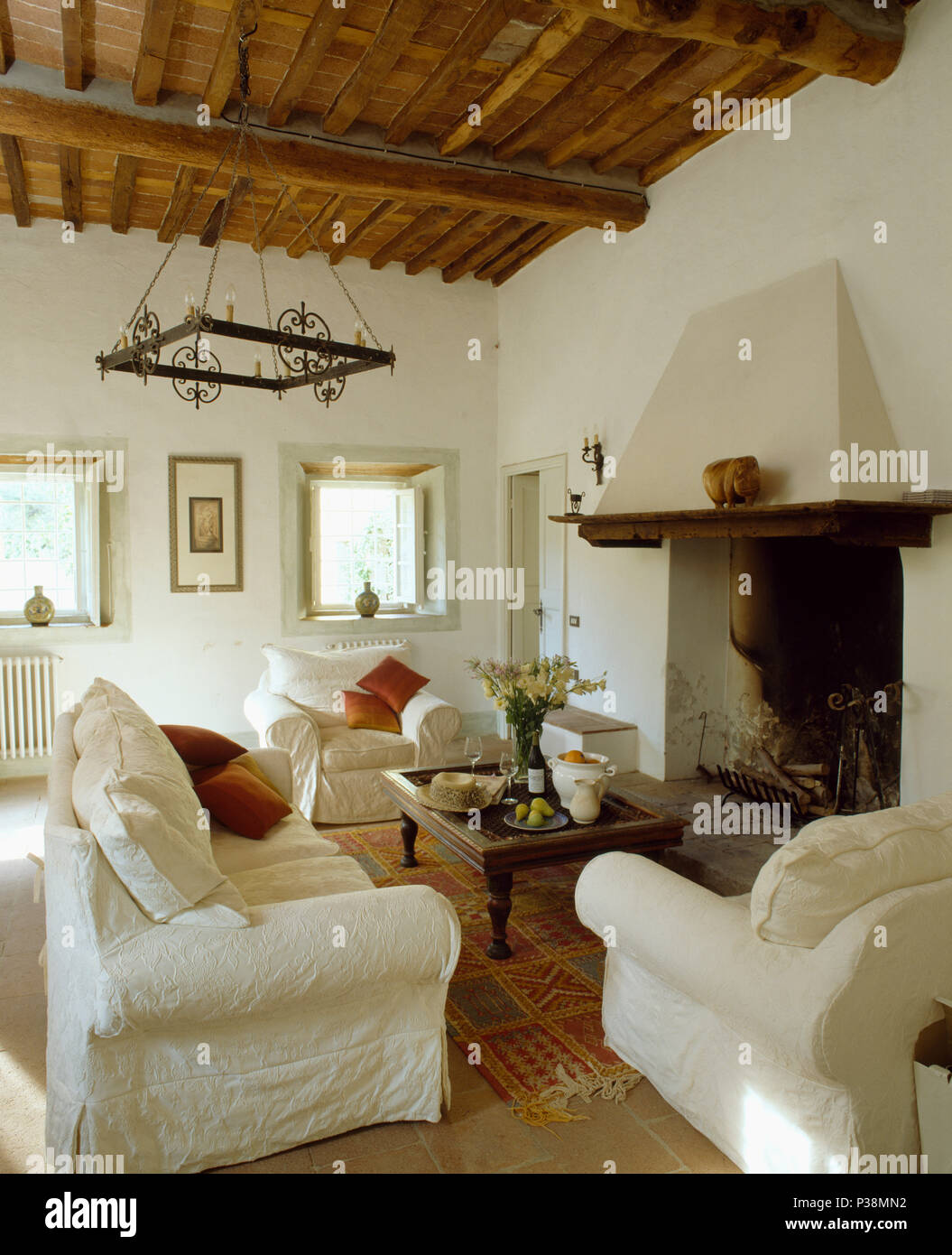 White Loose Covers On Sofa And Armchairs In Rustic Tuscan Living Room With Beamed Ceiling Low Table Front Of Fireplace
