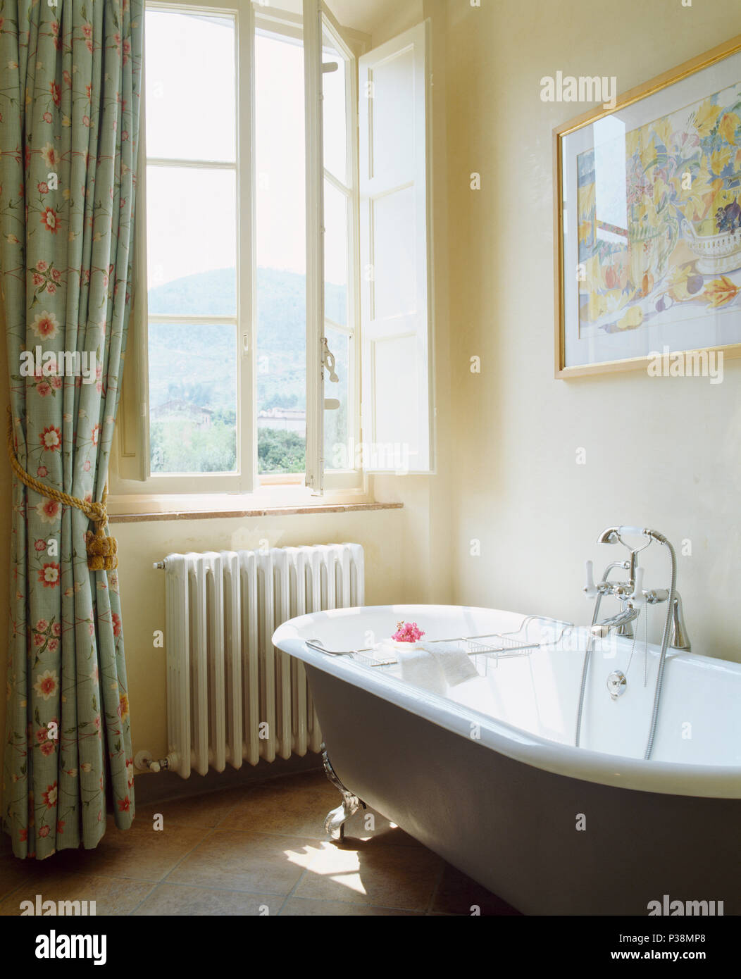 Roll-top bath in Tuscan bathroom with patterned pale blue curtains ...