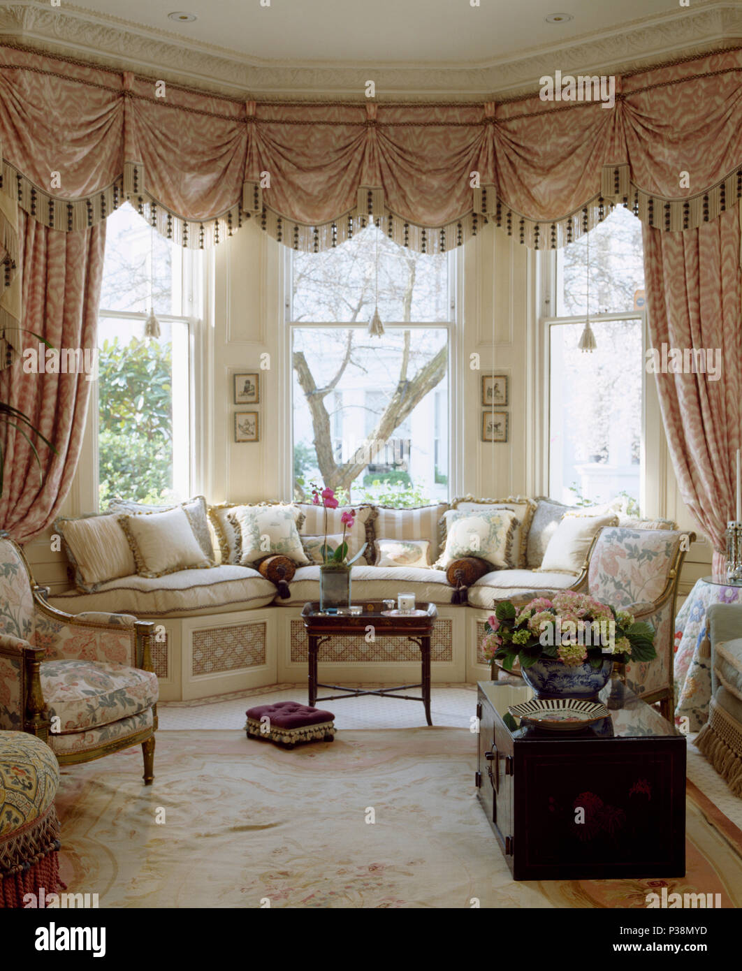 Ornate Swagged Pelmet And Silk Curtains On Bay Window In Townhouse