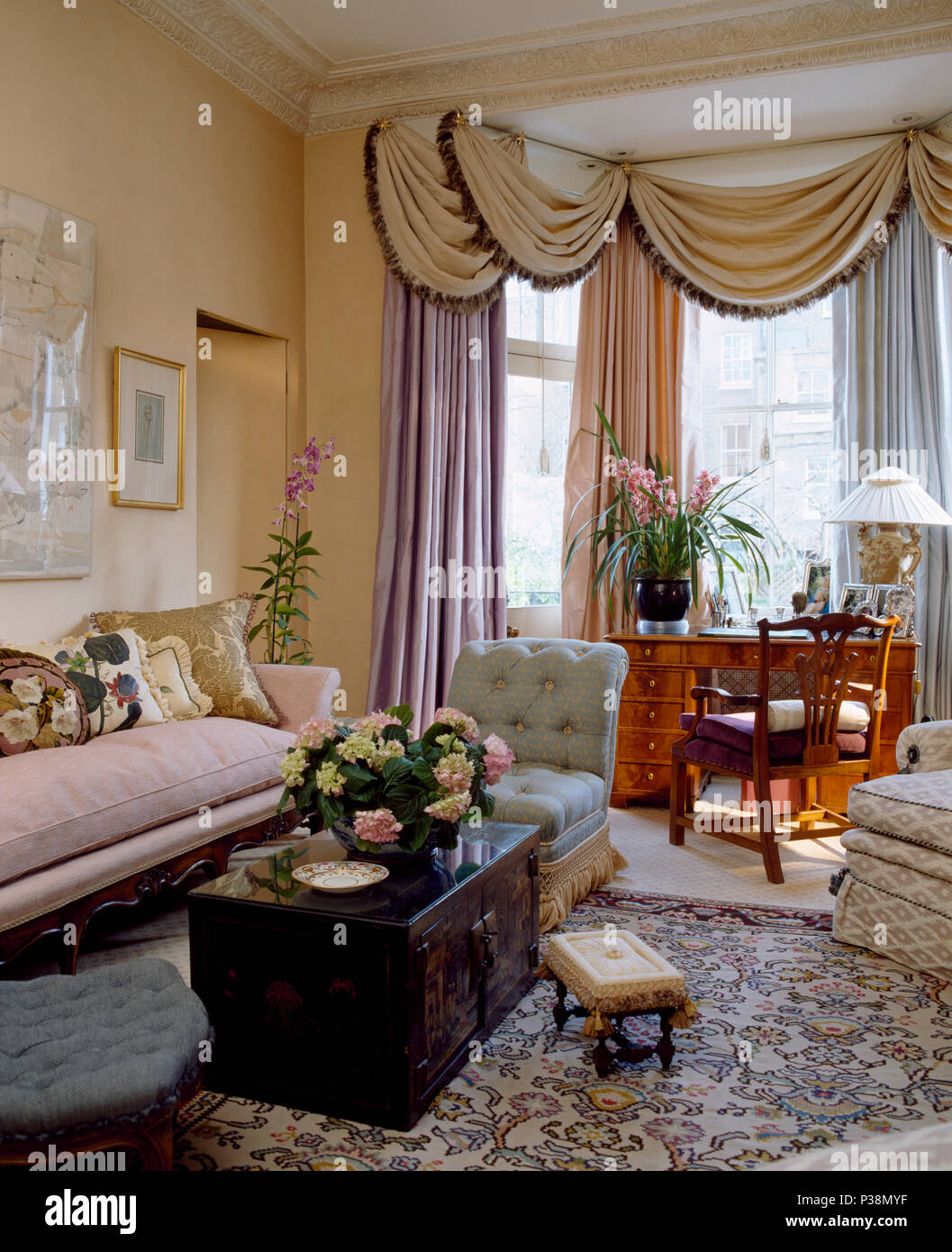 Swagged Pelmets And Silk Curtains On Bay Window In Opulent Townhouse Living  Room With Antique Wooden Chest