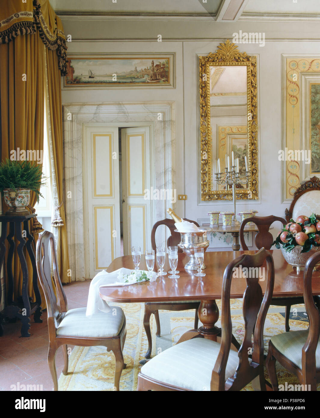 Antique Chairs At Table In Tuscan Dining Room With Gilt Antique Mirror On  Wall Beside Double Doors