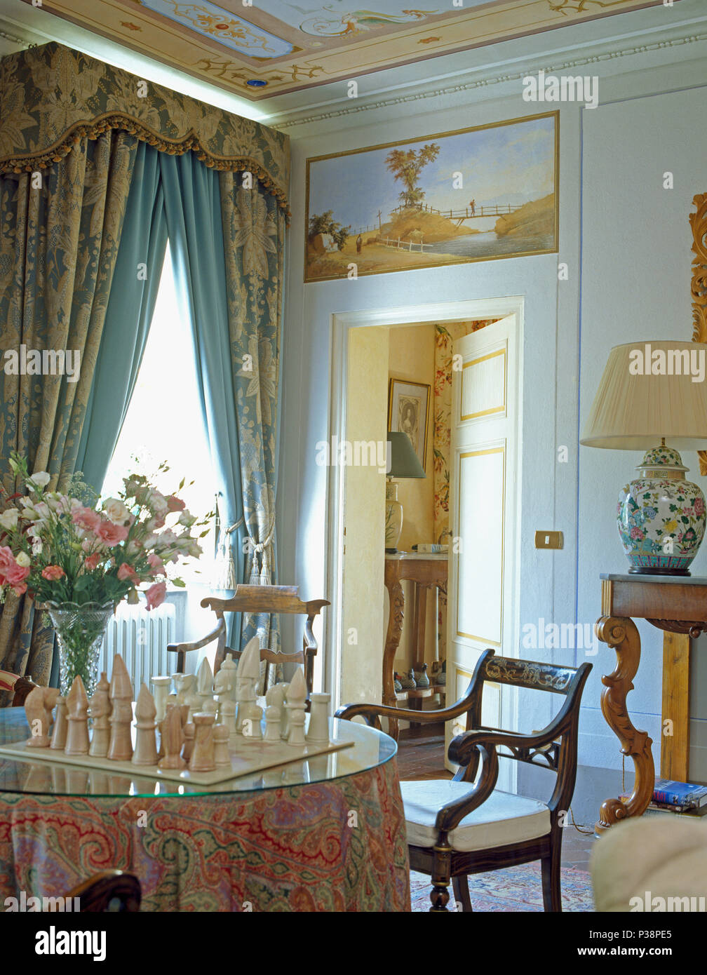 Chess Set On Dining Table With Patterned Cloth In Elegant Tuscan Dining Room  With Heavy Blue And Cream Curtains