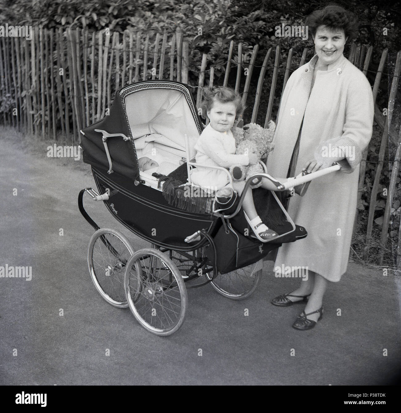 1950s Historical Picture Of A Mother Outside With Her Baby And Little Girl Sitting