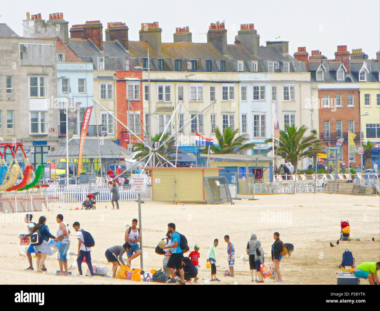 Weymouth, UK. 17th June 2018. Weymouth beach is surprisingly busy for such a chilly and overcast day Credit: stuart fretwell/Alamy Live News - Stock Image