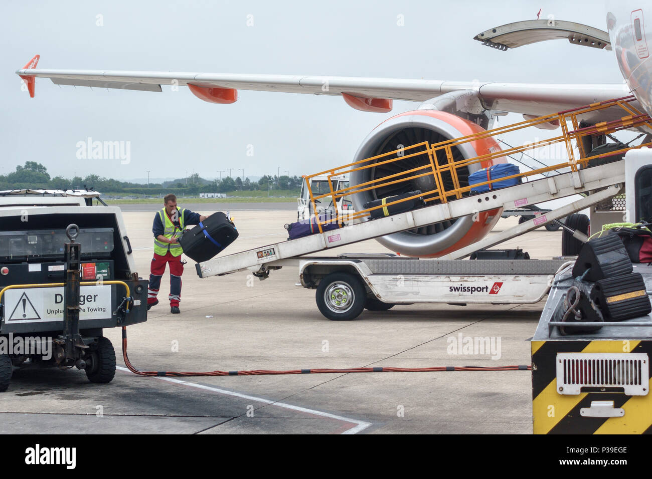 Bristol Airport, UK. A baggage handler loading suitcases onto an Easyjet aircraft - Stock Image