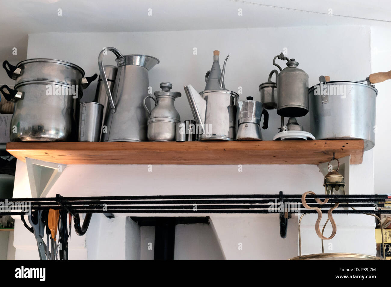 Open kitchen shelf with aluminium & stainless steel cooking objects including pots and jugs. In Adaptable House, 6 Doughty Mews, Bloomsbury, London. Stock Photo