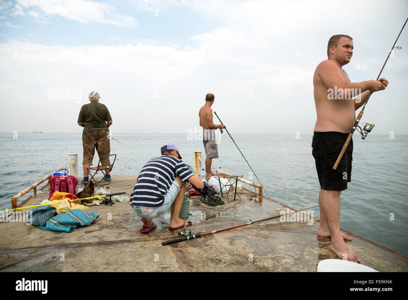 Odessa, Ukraine, anglers on a pier on the Black Sea - Stock Image
