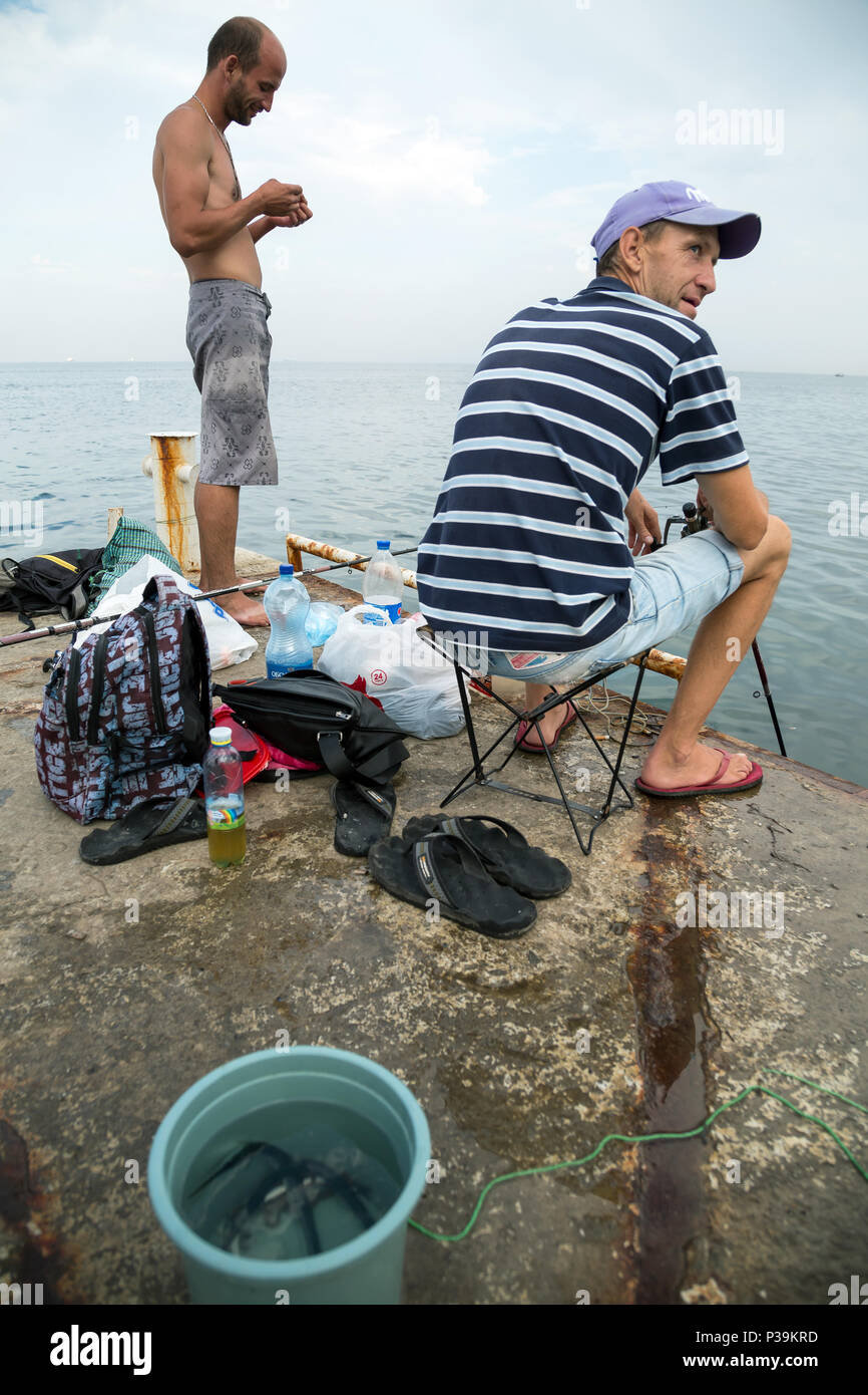 Odessa, Ukraine, anglers on a pier on the Black Sea - Stock Image