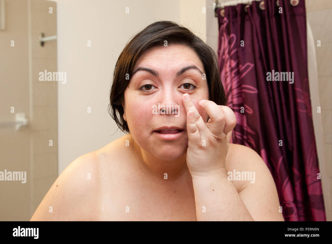 Woman touches and looks at the bags under her eyes with bare shoulders in the bathroom - Stock Image