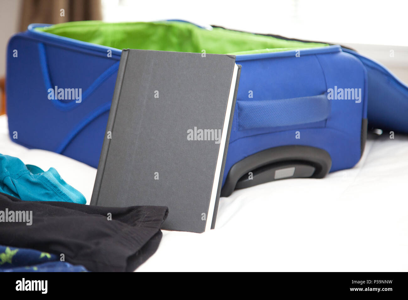 A hard cover black book with copy space beside an empty travel suitcase - Stock Image