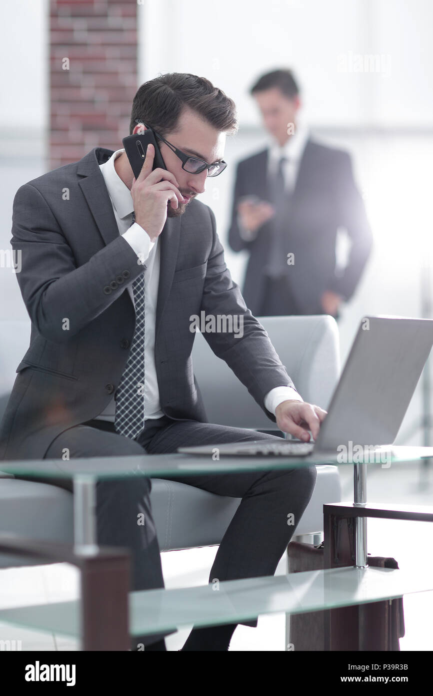 Portrait of businessman talking on mobile phone in office - Stock Image