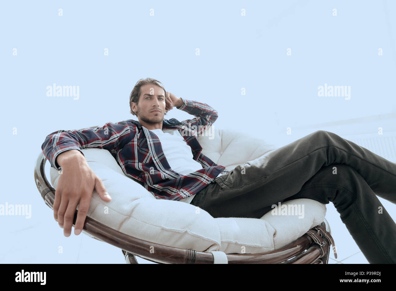 serious guy rests sitting in a large comfortable chair. side view. - Stock Image