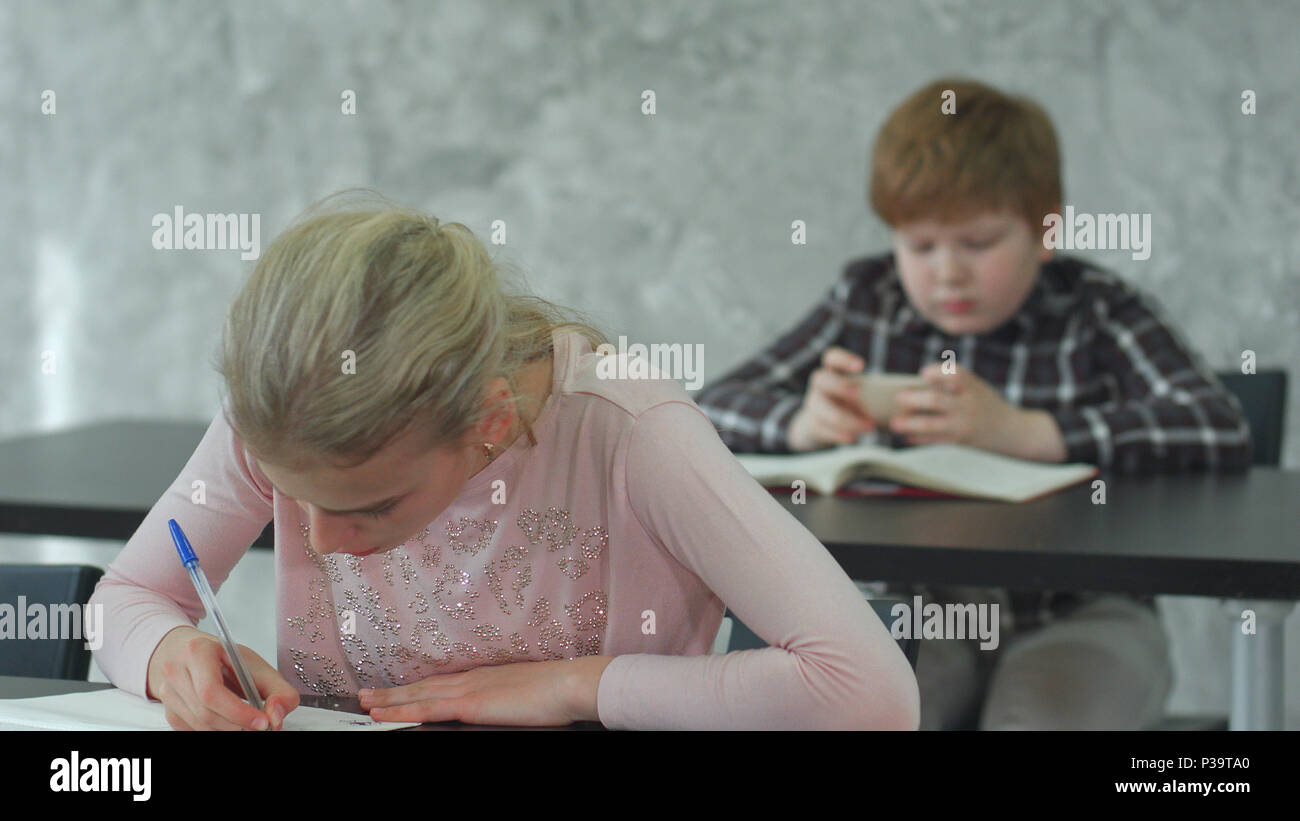 A young girl in a classroom concentrating on her test, while her classmate playing games on smartphone Stock Photo