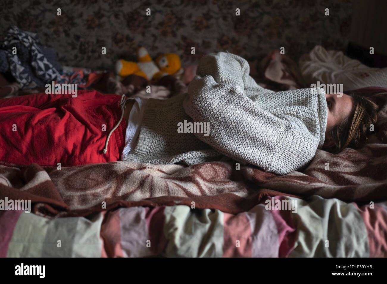 Caucasian woman closing her face with sweater lay on bed alone. She is upset, stressed with problems - Stock Image
