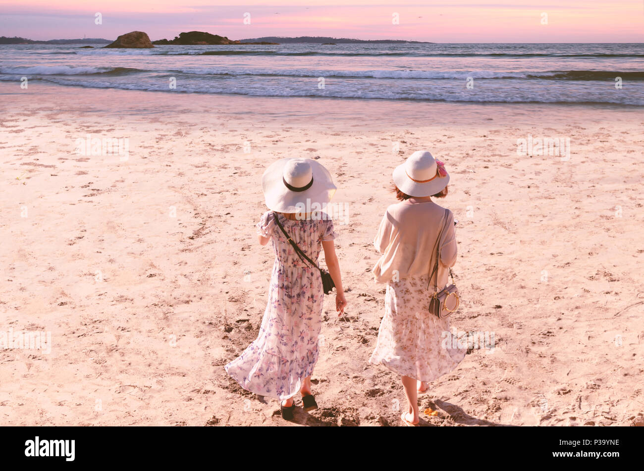 Two young friend  women in long dresses and hats walk along the beach to sea at evening sunset time. The concept of feminism, independence of women - Stock Image
