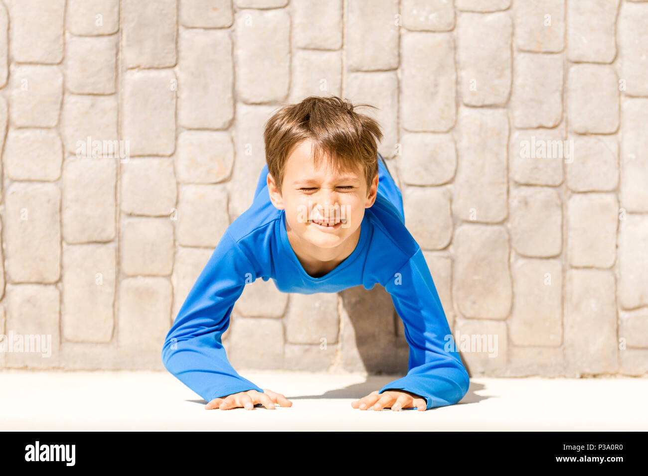 Top view of little boy looking up and enjoying the sun - Stock Image