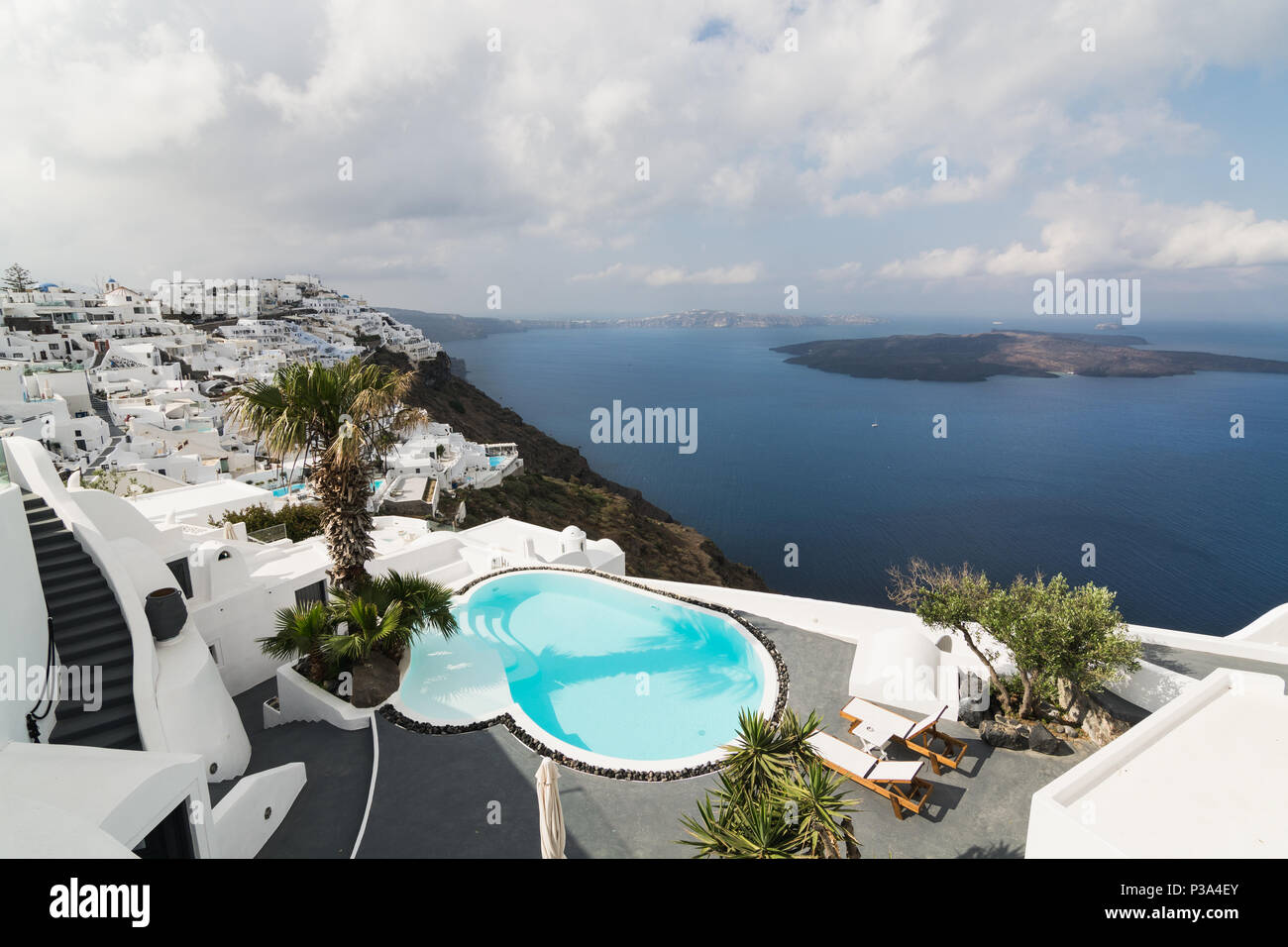SANTORINI, GREECE - MAY 2018: View over Aegean sea, Firostefani village and volcano caldera with luxury hotel and infinity swimming pool Stock Photo