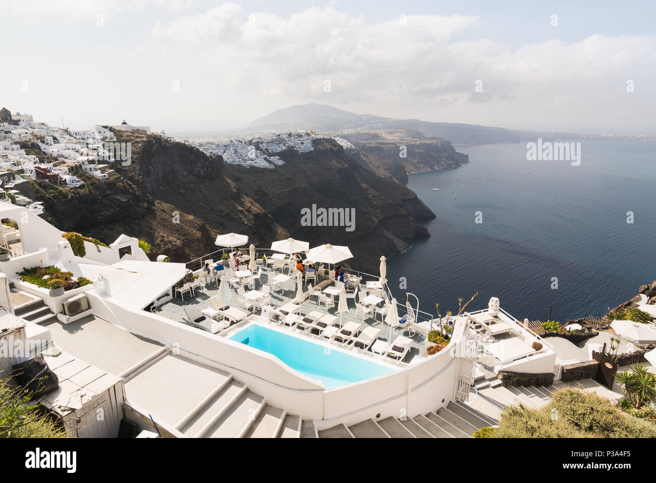 SANTORINI, GREECE - MAY 2018: View over Aegean sea, Firostefani village and volcano caldera with luxury hotel and infinity swimming pool on the foregr Stock Photo