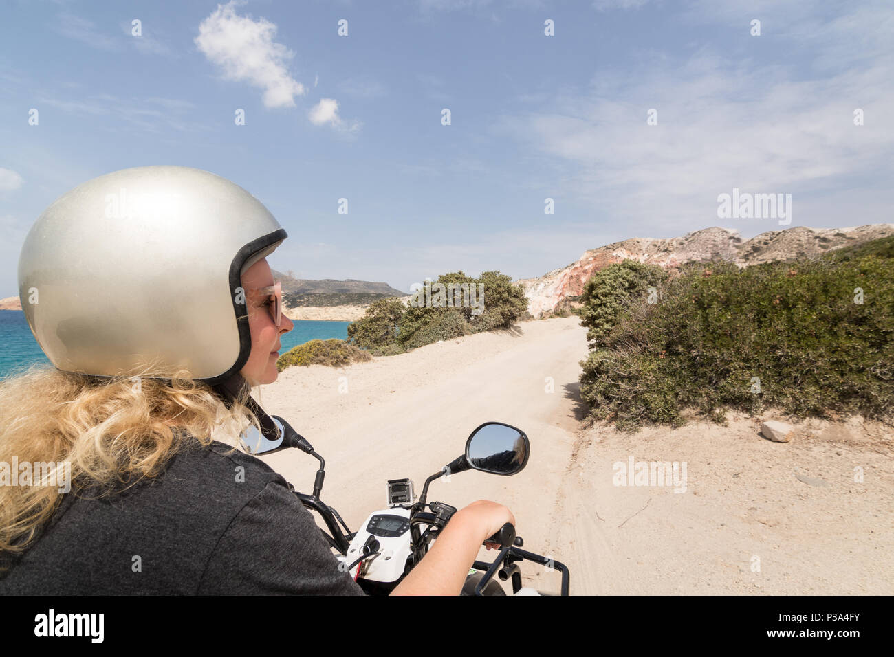 Young Woman Driving Rental Quad Bike On Seaside Road In Milos Island