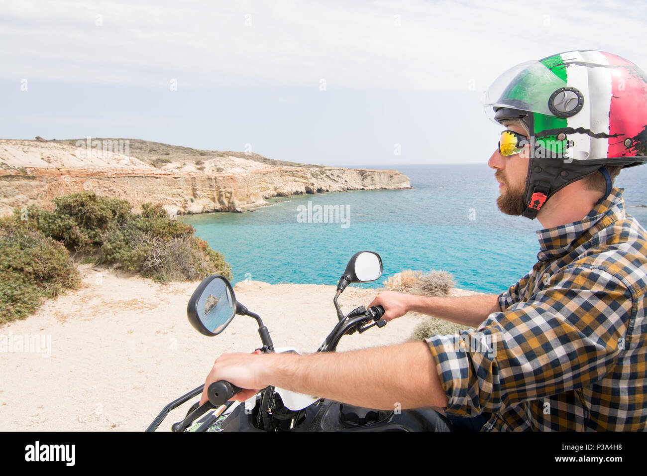 Young Man Driving Rental Quad Bike On Seaside Road In Milos Island